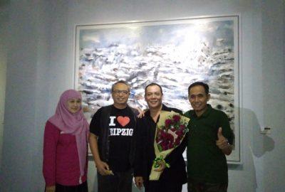 Sitok Srengenge (kedua dari kanan) berpose di depan karyanya bersama para pengunjung pameran lukisannya di Langit Art Space, Yogyakarta, Kamis (18/5). Pembukaan pameran malam itu diwarnai aksi penolakan. (Foto: Mega Nur/Serunai)
