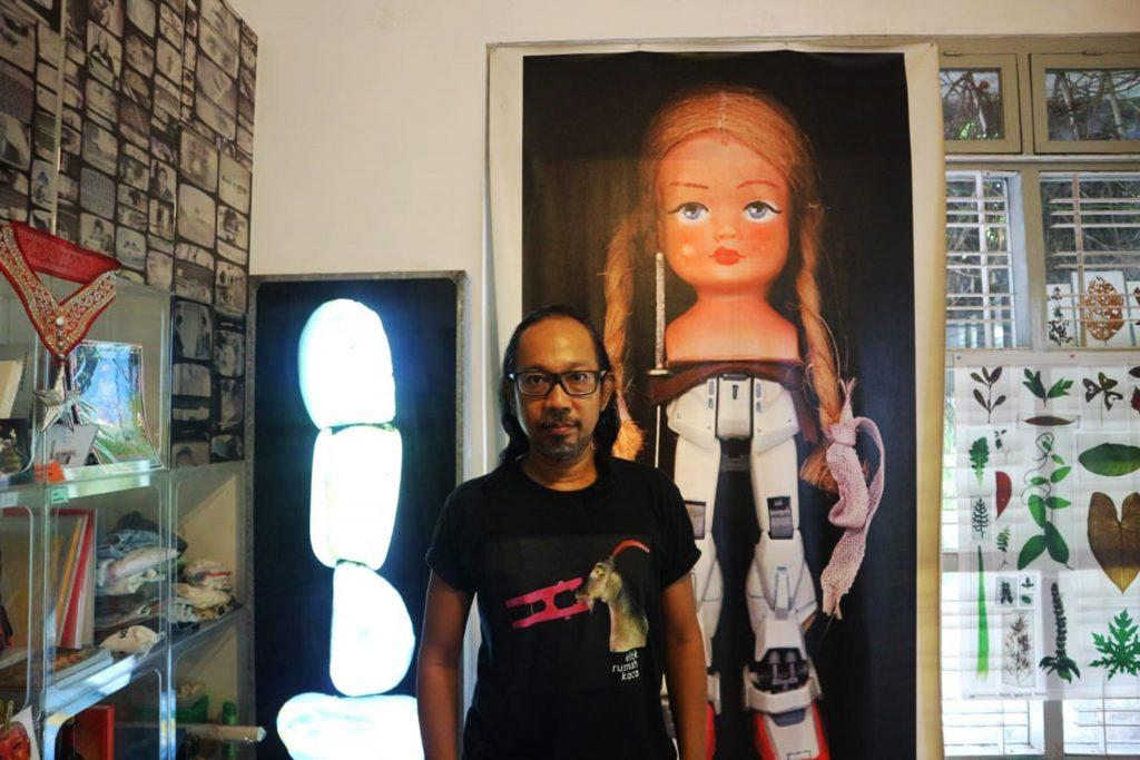 Angki Purbandono mengenakan kaos sampul album Kamar Gelap milik band Efek Rumah Kaca. Ia berpose di depan Gundam, salah satu karyanya yang termahsyur (Foto; Ayub Basyir)